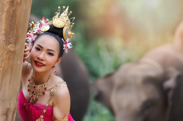 Les jolies filles thaïlandaises en costumes traditionnels thaïlandais touchent un arbre