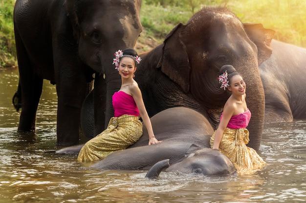 Jolies filles thaïlandaises en robe thaïlandaise traditionnelle avec des éléphants