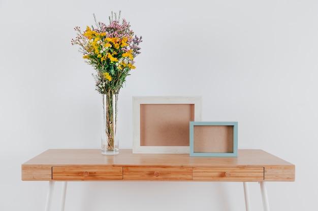 Jolies fleurs près des cadres sur la table