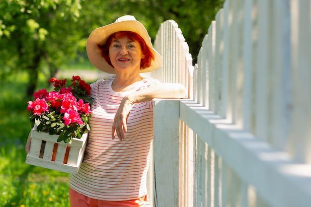 Jolies fleurs roses. belle femme rousse âgée portant un chapeau d'été tenant de belles fleurs roses
