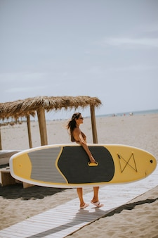 Jolies jeunes femmes avec paddle board sur la plage un jour d'été