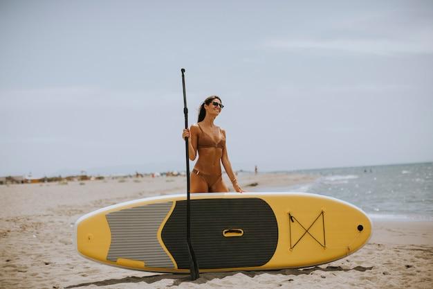 Jolies jeunes femmes avec paddle sur la plage un jour d'été