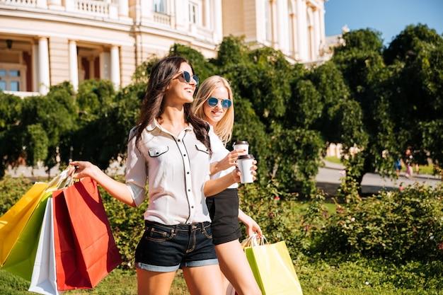 Jolies jeunes femmes avec des sacs à provisions s'amusant à marcher dans la rue