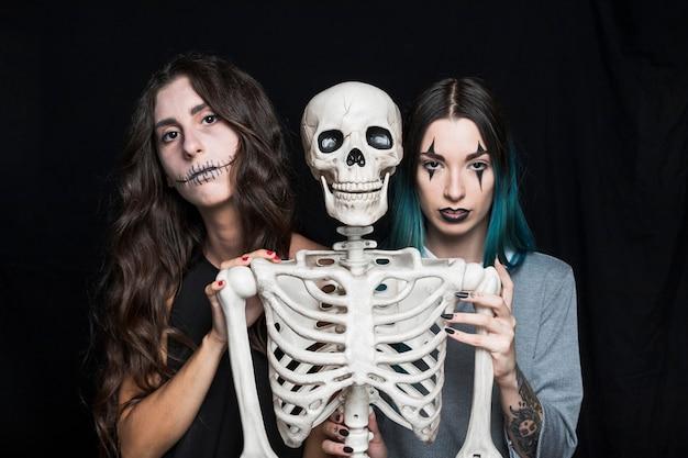 Jolies jeunes femmes avec squelette en plastique