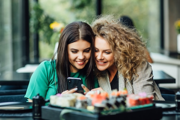Jolies jeunes filles, partenaires regardant sur le téléphone portable avec assiette de sushis sur table. terrasse de restaurant moderne.