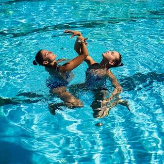 Jolies jeunes filles posant dans l'eau