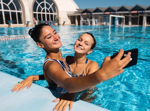 Jolies jeunes filles prenant un selfie à la piscine