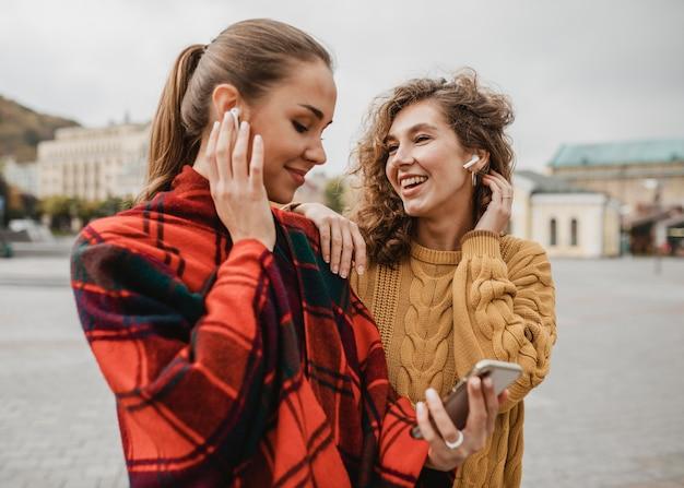 Jolies jeunes filles vérifiant un téléphone ensemble