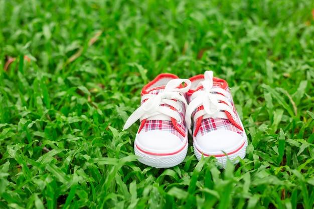 Jolies petites chaussures de bébé rouges et blanches sur l'herbe verte