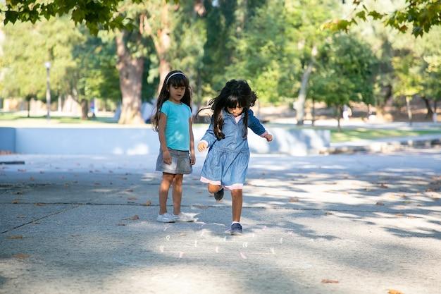 Jolies petites filles aux cheveux noirs jouant à la marelle dans le parc de la ville. pleine longueur, copiez l'espace. concept de l'enfance