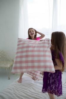 De jolies petites filles en robes de princesse roses et violettes se battent avec des coussins