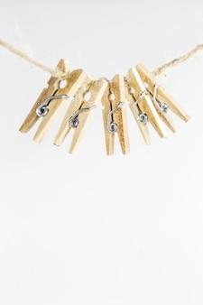 Jolies petites pinces à linge décoratives pèsent sur la corde, isolé sur blanc