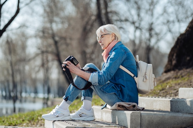 Jolies photos. alerte femme mûre assise sur les marches et regardant à travers les photos