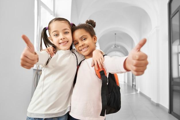 Jolies, positives, écolières gaies, étreignant et montrant les pouces vers le haut.