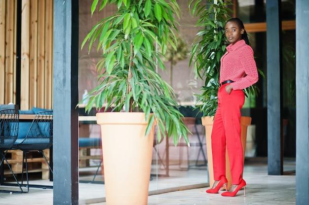 Jolies tresses affaires dame afro-américaine brillante personne autoritaire amicale porter une chemise et un pantalon rouges de bureau.