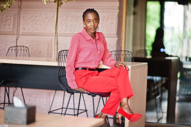 Jolies tresses affaires dame afro-américaine lumineuse autoritaire personne amicale porter une chemise et un pantalon rouges de bureau, assis sur une chaise.