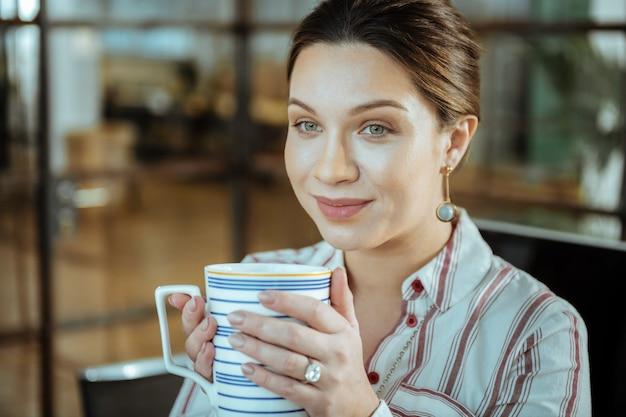 Jolis bijoux. gros plan sur une belle femme brune élégante portant de beaux bijoux buvant du thé