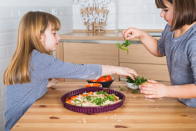 Jolis enfants cuisinant des pizzas maison ensemble dans la cuisine