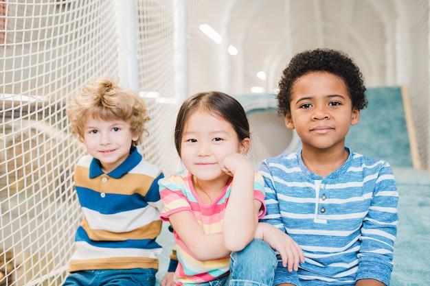 Jolis garçons et filles reposants d'ethnies asiatiques, caucasiennes et africaines, passer du temps sur l'aire de jeux au centre de loisirs