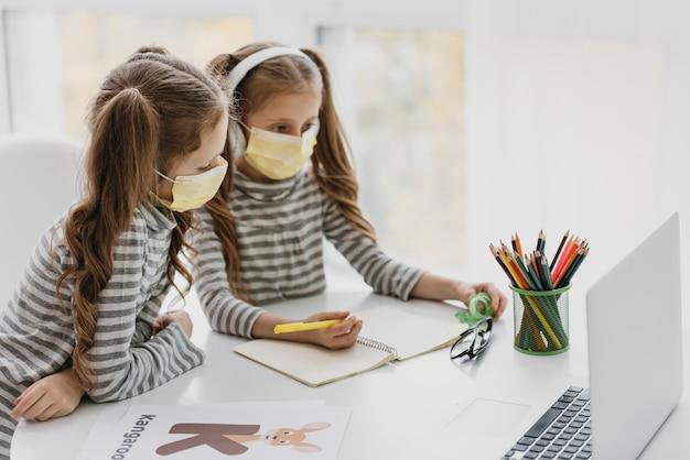 Jolis jumeaux portant des masques médicaux à l'intérieur