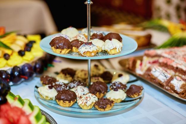De jolis petits cupcakes blancs et bruns se dressent sur le plat fatigué