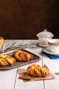 Jolis petits pains noués à la cannelle sur une table en bois blanc