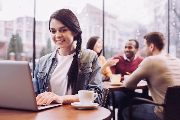 Jolly femme heureuse enthousiaste regardant l'écran tout en regardant vers le bas et posant au café