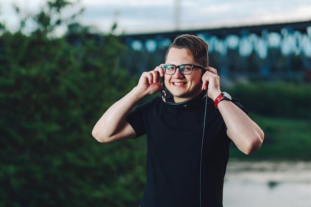 Jolly guy souriant posant avec des écouteurs en plein air
