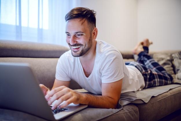 Jolly homme caucasien non rasé en pyjama allongé sur le ventre sur le canapé dans le salon et à l'aide d'un ordinateur portable.