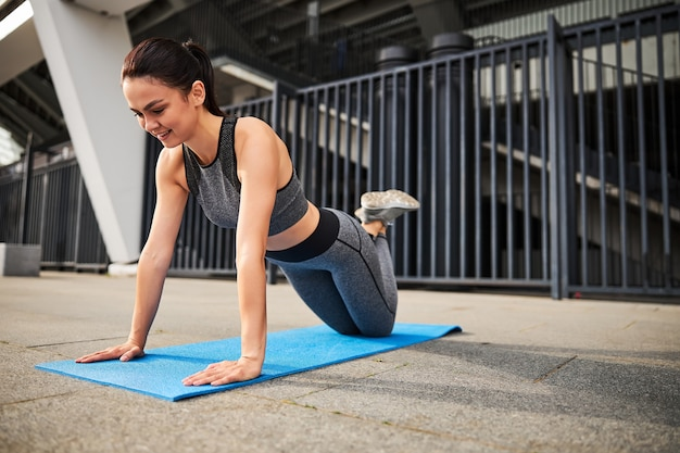 Jolly jeune femme mince entraîne le haut du corps et le noyau sur un tapis dans le centre-ville