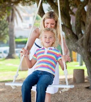 Jolly mère poussant sa fille sur une balançoire