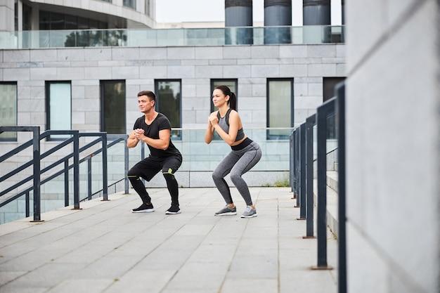 Jolly slim femme et homme font des squats pendant l'entraînement sur l'escalier à l'extérieur dans le centre urbain