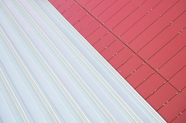 Jonction de deux textures: carreaux rectangulaires en métal rouge et tôle ondulée en métal blanc
