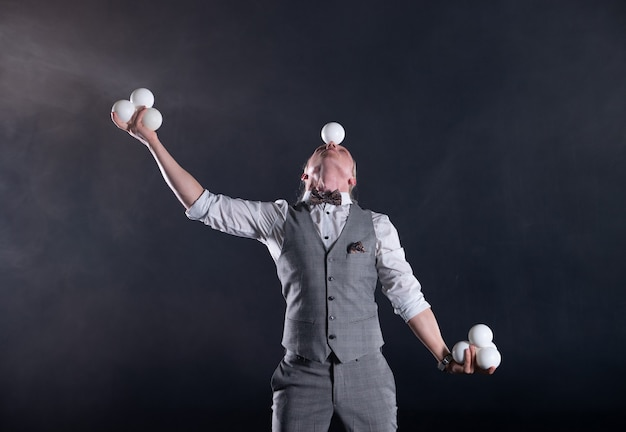 Jongleur vêtu d'un costume comme un homme d'affaires avec des boules blanches. concept de réussite et de gestion.