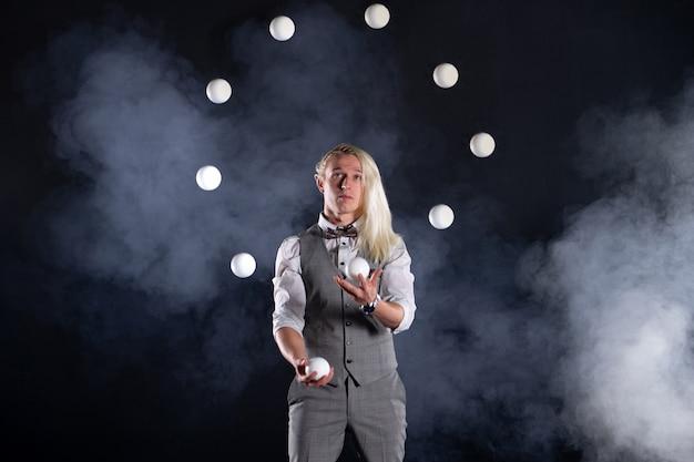 Jongleur vêtu d'un costume comme un homme d'affaires lançant des boules blanches. concept de réussite et de gestion.