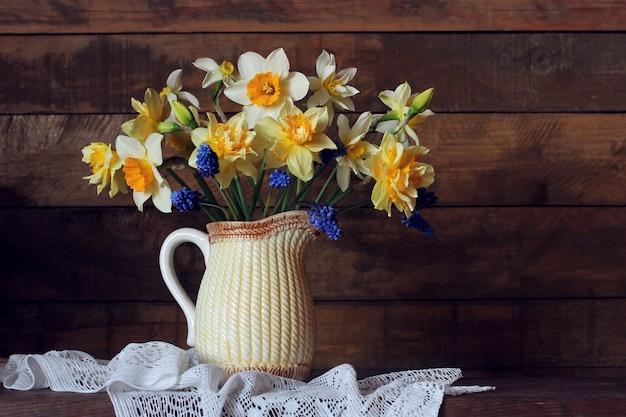 Jonquilles dans un pichet sur la table. bouquet de fleurs de jardin