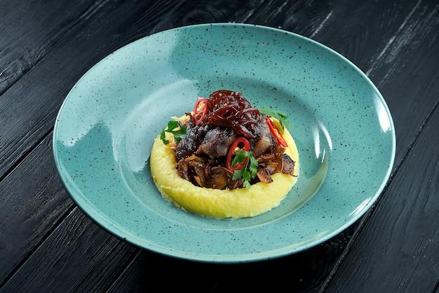Joue de boeuf grillée garnie de purée de pommes de terre dans une assiette bleue sur fond de bois noir.