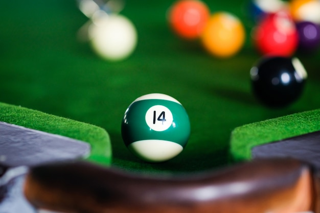 Jouer au billard ou se préparer à tirer des balles de billard sur une table de billard verte.