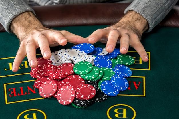 Jouer au poker. jetons sur la table verte. puces dans les mains des hommes