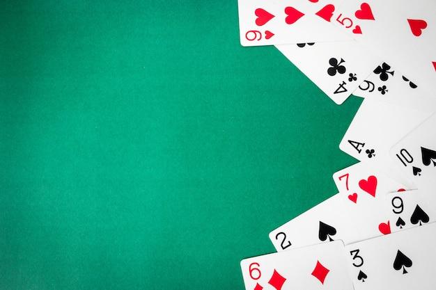 Jouer aux cartes sur fond vert. espace libre pour le texte