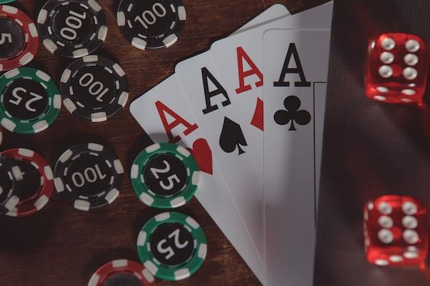 Jouer aux jetons de cartes de dés rouges avec as et gros plan d'ordinateur portable