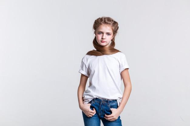 Jouer avec les cheveux. calme jolie fille aux cheveux longs posant devant la caméra tout en portant un t-shirt uni et un jean bleu