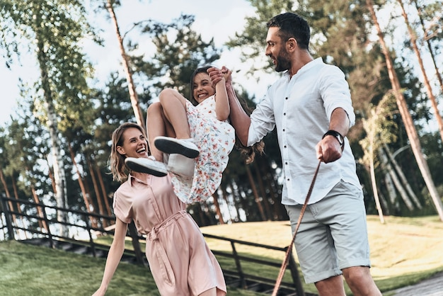 Jouer ensemble. mère et père balançant sa fille et souriant en marchant dans le parc