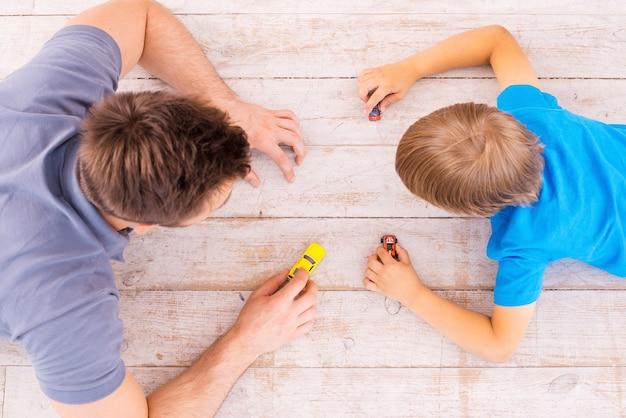 Jouer ensemble. vue de dessus du père et du fils allongés sur le parquet et jouant ensemble avec des petites voitures
