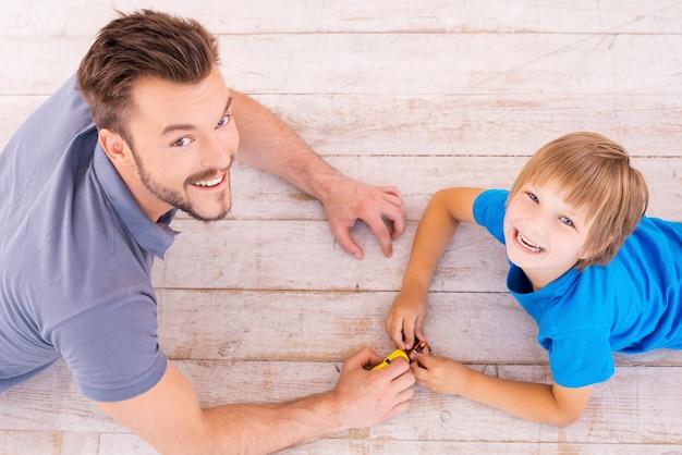 Jouer ensemble. vue de dessus de l'heureux père et fils jouant à des petites voitures et levant les yeux avec le sourire en position couchée sur le plancher de bois franc ensemble