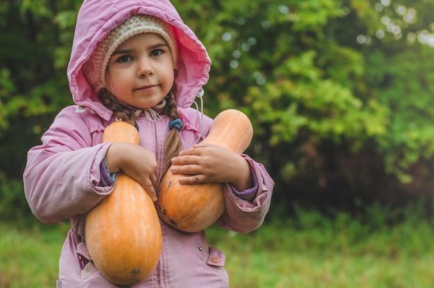 Jouer à l'extérieur mignonne petite fille tenant une citrouille. récolte de citrouilles
