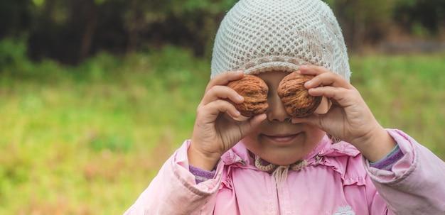 Jouer à l'extérieur mignonne petite fille tenant une noix devant elle. les récoltes de noix. l'automne dans le jardin, la jolie fille et les grosses noix.