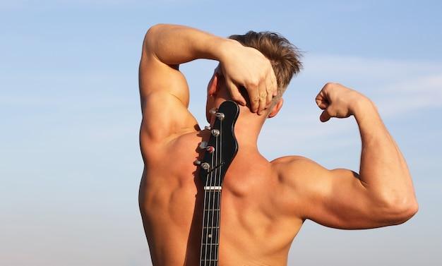 Jouer de la guitare. guitare électrique. homme avec beau torse. santé, caucasien athlétique, musclé.