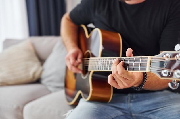 Jouer de l'instrument. l'homme en vêtements décontractés et avec guitare acoustique est à l'intérieur.