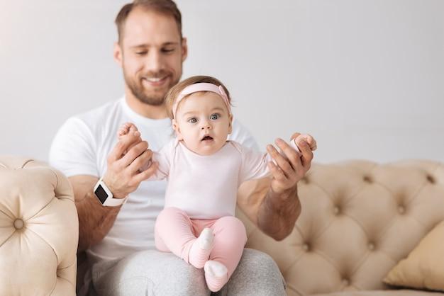 Jouer à des jeux ensemble. enthousiaste homme barbu positif assis sur le canapé à la maison et étreignant son enfant tout en exprimant la positivité et en jouant à des jeux